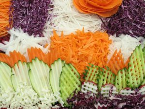 Chopped vegetables in purple, white, orange, and green