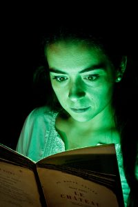 Woman lit with green light coming from a book