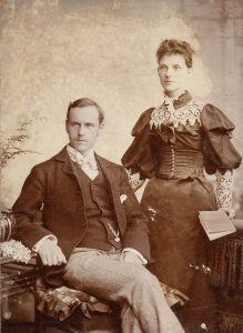 Sepia-tone photo of a seated man and standing woman, 1895