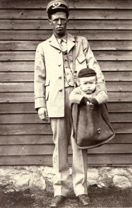 Uniformed postal employee with a child in a mail sack