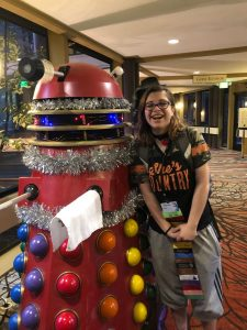 Red Dalek on the left and teenage girl on the right