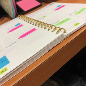 Open planner book with brightly colored sticky note flags throughout the page