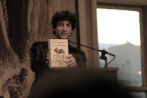 Neil Gaiman holding a copy of Good Omens
