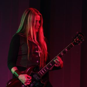 White woman with long blond hair playing electric guitar