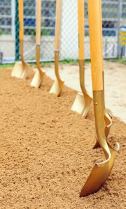 Six gold-painted shovels stuck into dirt